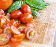 Cherry tomatoes and basil. Freshly chopped cherry tomatoes and basil on a chopping board Stock Image