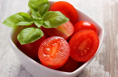 Cherry tomatoes with basil in glass bowl, healthy food and nutrition Stock Image
