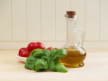 Cherry tomatoes, basil herbs and olive oil. Ingredients for cooking. Royalty Free Stock Photos