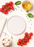Tomatoes, basil, mozzarella cheese. Caprese salad ingredients. Cherry tomatoes, basil leaves, mozzarella cheese, olive oil and pepper mix around light stone Royalty Free Stock Photos