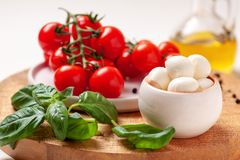 Tomatoes, basil, mozzarella cheese. Caprese salad ingredients. Cherry tomatoes, basil leaves, mozzarella cheese, olive oil and pepper mix on round wooden cutting Stock Photography