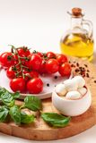 Tomatoes, basil, mozzarella cheese. Caprese salad ingredients. Cherry tomatoes, basil leaves, mozzarella cheese, olive oil and pepper mix on round wooden cutting Stock Images
