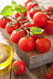 Cherry tomatoes basil and olive oil over wooden background Royalty Free Stock Photos