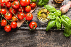 Cherry Tomatoes, basil and olive oil on wooden background, top view royalty free stock images