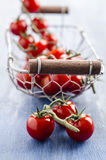 Cherry tomatoes. In a basket on a blue background Stock Photo