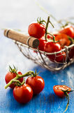 Cherry tomatoes. In a basket on a blue background Royalty Free Stock Photo