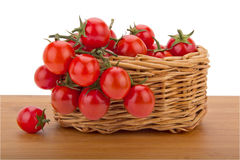 Cherry tomatoes in a basket isolated on white back. Composition of the basket of tomatoes on a wooden table top Stock Images