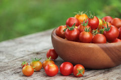 Cherry tomatoes in a basket on old wooden surface Stock Photos