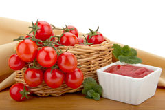 Cherry tomatoes in a basket and tomato paste. Photo depicting a basket of tomatoes, tomato paste and cloth Stock Image