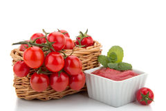 Cherry tomatoes in a basket and tomato paste. Composition of the basket of tomatoes and tomato paste with the cups Stock Photo