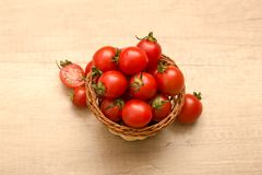 Cherry tomatoes in a basket on a wooden background. Some Cherry tomatoes in a basket on a wooden background Royalty Free Stock Photo