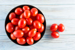 Cherry tomatoes in a black bowl on aged table Royalty Free Stock Images