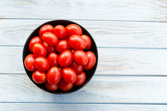 Cherry tomatoes in a black bowl on aged table Stock Image
