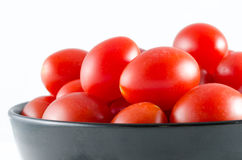 Cherry tomatoes in a black bowl isolated on white Stock Images