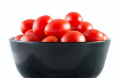 Cherry tomatoes in a black bowl isolated on white Stock Photo