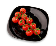 Cherry tomatoes on the black plate. Isolated image of cherry tomatoes on a black plate on a white background Stock Photo