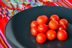 Cherry tomatoes in a black plate over colorful Mexican table top Stock Images