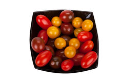 Cherry tomatoes in black plate on white Stock Image