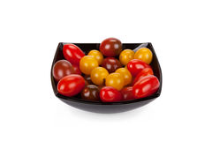 Cherry tomatoes in black plate on white Royalty Free Stock Images