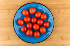 Cherry tomatoes in blue glass plate on wooden table Stock Image