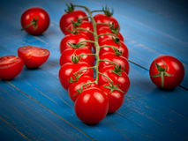 Cherry tomatoes. On blue wooden background Royalty Free Stock Images