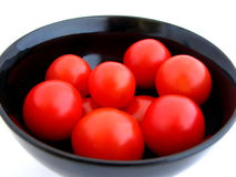 Cherry tomatoes in Bowl. Black bowl of cherry tomatoes isolated on white background Stock Image