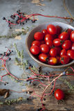 Cherry tomatoes on bowl on rustic blue wooden table Stock Photography