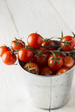 Cherry tomatoes on branch in metal bucket on a wooden background.  Stock Photo