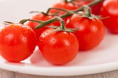 Cherry tomatoes on a branch in a plate Royalty Free Stock Photography