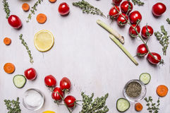 Cherry tomatoes on a branch with Sliced cucumber lemon carrots various herbs seasoning salt lined frame place for text on wooden r Royalty Free Stock Photography