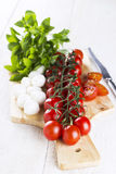 Cherry tomatoes on branch and the tomatoes cut on slices, cheese. Mozzarella, fresh basil and knife on wooden board Royalty Free Stock Photography