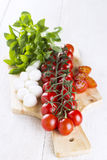 Cherry tomatoes on branch and the tomatoes cut on slices, cheese. Mozzarella, fresh basil on wooden board Royalty Free Stock Photography