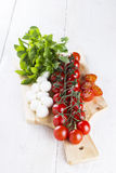 Cherry tomatoes on branch and the tomatoes cut on slices, cheese. Mozzarella, fresh basil on wooden board and white table Stock Photography