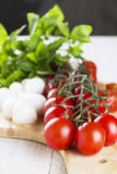 Cherry tomatoes on branch and the tomatoes cut on slices, cheese. Mozzarella, fresh basil on wooden board and white table - a close up Stock Images