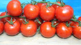 Cherry tomatoes on the branches that lie on the kitchen board sprinkle or pour water or chemicals. May be processed. Before use. Drops on tomatoes. Close-up stock footage