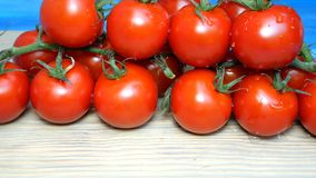 Cherry tomatoes on the branches that lie on the kitchen board sprinkle or pour water or chemicals. May be processed. Before use. Drops on tomatoes. Close-up stock video