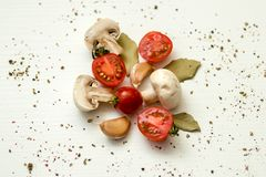 Cherry tomatoes, champignons, bay leaves and garlic on a white background Royalty Free Stock Image