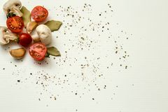 Cherry tomatoes, champignons, bay leaves and garlic on a white background. Vegetarian Stock Photography