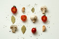 Cherry tomatoes, champignons, bay leaves and garlic on a white background. Vegetarian Stock Photo