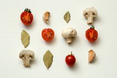 Cherry tomatoes, champignons, bay leaves and garlic on a white background. Vegetarian Royalty Free Stock Images