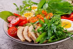 Cherry tomatoes, chicken breast, eggs, carrot, salad with arugula. Plate with a keto diet food. Cherry tomatoes, chicken breast, eggs, carrot, salad with arugula stock photo