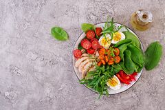 Cherry tomatoes, chicken breast, eggs, carrot, salad with arugula. Plate with a keto diet food. Cherry tomatoes, chicken breast, eggs, carrot, salad with arugula royalty free stock image