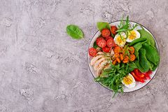 Cherry tomatoes, chicken breast, eggs, carrot, salad with arugula royalty free stock images