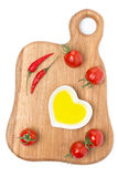Cherry tomatoes, chilli and olive oil on wooden board, isolated Stock Image