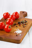 Cherry tomatoes with color pepper and sea salt. On a brown kitchen board on a white wooden surface Royalty Free Stock Images
