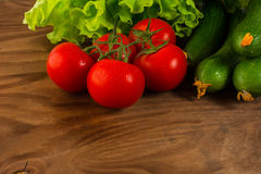 Cherry tomatoes and cucumber on wooden table Stock Images