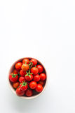 Cherry tomatoes are in a cup on a white background. Fresh cherry tomatoes are in a cup on a white background royalty free stock photography
