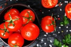 Cherry Tomatoes découpé en tranches frais sur un fond noir avec des épices sel brut et herbes Vue supérieure, utilisation en tant photo stock