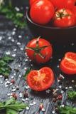 Cherry Tomatoes d?coup? en tranches frais sur un fond noir avec des ?pices sel brut et herbes photographie stock