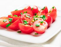 Cherry tomatoes decorated with green onions. Stock Photography
